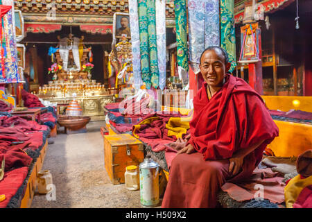 Monk sitting in prayer hall. - Stock Photo