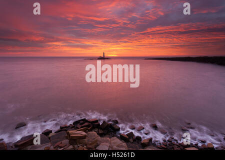 A vibrant red and orange sunrise looking across the bay to St Mary's Lighthouse, Whitley Bay at high tide from the - Stock Photo