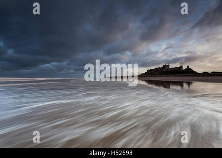Bamburth castle and beach on the Northumberland coast after sunset with the rush of the waves as the tide goes out, - Stock Photo