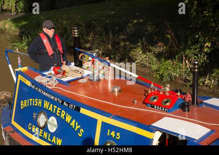 UK, England, Cheshire, Beeston Brook, man steering narrowboat Greenlaw  on Shropshire Union Canal below Beeston - Stock Photo
