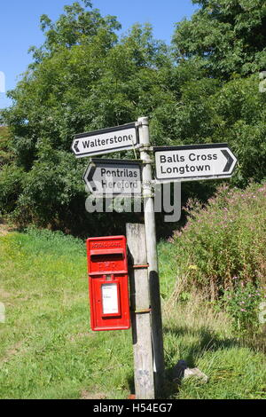 Road sign and Royal Mail post box, Rowlestone, Herefordshire, England - Stock Photo