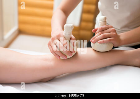 Masseuse doing thai massage with salt bags - Stock Photo