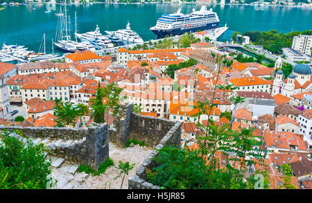 The ruins of the old Venetian fortress with red tile roofs and cruise liner in harbour, Kotor Montenegro - Stock Photo