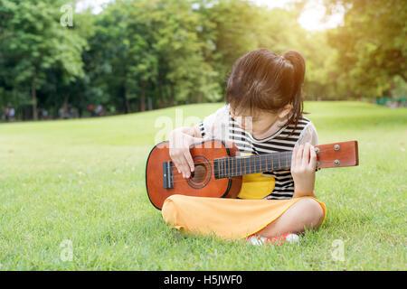 Asian little kids girl sitting on grass and play ukulele in park. Kids funny playing ukulele - Stock Photo