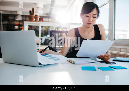 Portrait of young asian woman reading documents at her desk. Businesswoman at her workplace doing paperwork. - Stock Photo