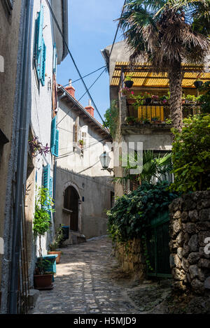 Narrow lane with cobblestones in the Old Town, Town of Krk on the island of Krk, Croatia - Stock Photo