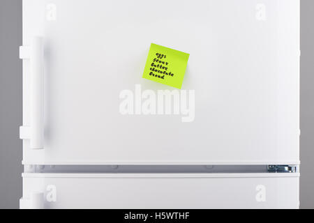 List of words eggs, flour, butter, chocolate, bread written on green sticky note paper on white refrigerator door - Stock Photo