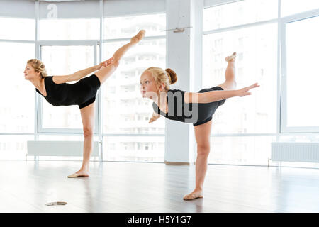 Beautiful young woman and little girl ballerina dancing in ballet school - Stock Photo