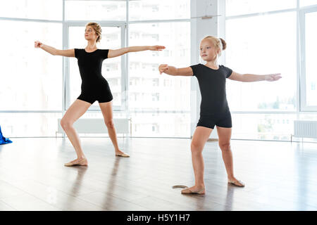 Cute little girl ballerina dancing with her teacher in dance studio - Stock Photo