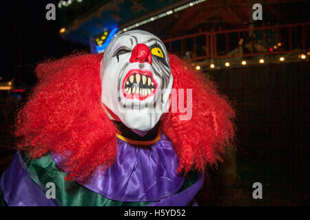 A killer Halloween clown with mask, white face, red hair wig,  and a screaming scary expression, Southport, Merseyside, - Stock Photo