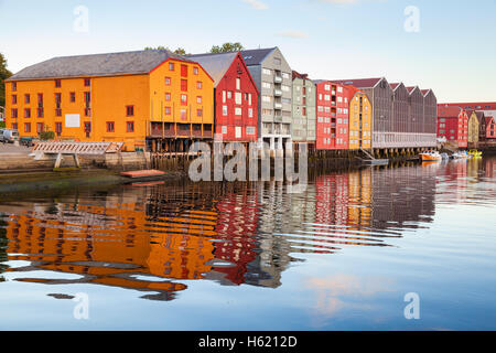 Colorful old wooden houses stand in a row along the river coast. Trondheim, Norway - Stock Photo