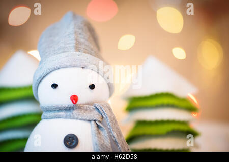 Detail of cute festive snowman with Christmas lights in background - Stock Photo