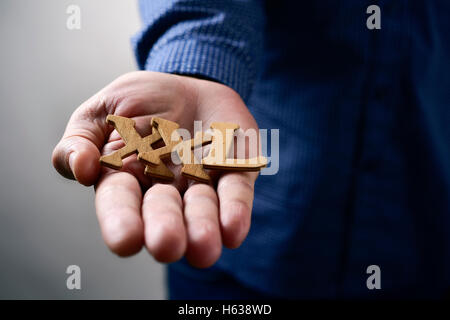 closeup of some wooden letters forming the expression XXL, for extra extra large, in the hand of a young caucasian - Stock Photo