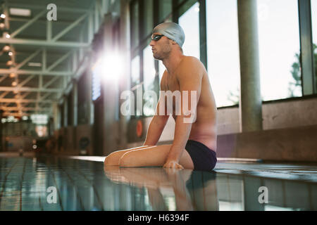 Side view shot of fit young male swimmer relaxing at the edge of a swimming pool. - Stock Photo