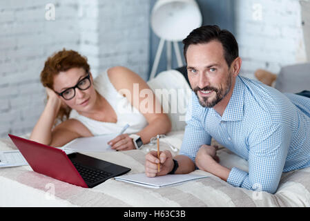 Bearded man making notes while lying on bed with wife - Stock Photo