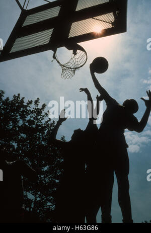 Players fighting for a rebound during street basketball game in 'the cage' in New York City's Greenwich Village, - Stock Photo