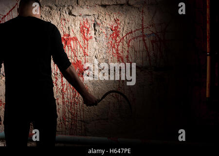 Shadowy male figure holding sickle near blood stained wall for concept about murder and scary Halloween holiday - Stock Photo