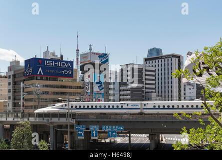 Shinkansen bullet train on a bridge in Shiodome, Minato, Tokyo, Japan - Stock Photo