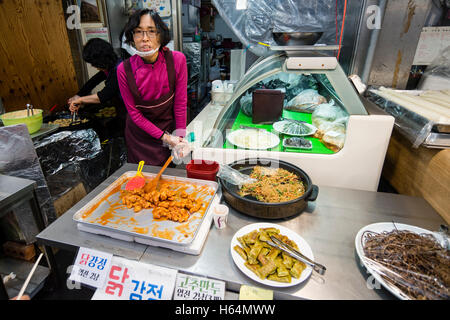 A female vendor selling dakgangjeong (fried sweet crispy chicken) at a food stall in Tongin Market, Jongno-gu, Seoul, - Stock Photo