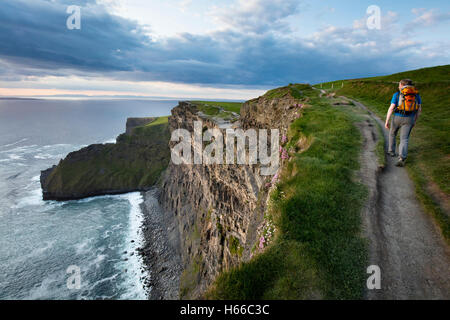 Hiker on top of the Cliffs of Moher, County Clare, Ireland. - Stock Photo