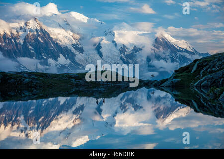 Hikers and the Mont Blanc massif reflected in Lac des Cheserys. Chamonix Valley, French Alps, France. - Stock Photo