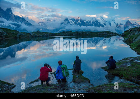 Photographers beside Lac des Cheserys, beneath the Mont Blanc massif, Chamonix Valley, French Alps, France. - Stock Photo