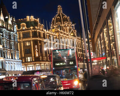 SALES LONDON Harrods department store at dusk with lit 'Sale' sign shoppers red bus taxis & traffic  Knightsbridge - Stock Photo