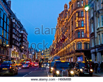 Brompton Road shops including Harrods store at dusk with lit 'Sale' sign shoppers red buses and taxis Knightsbridge - Stock Photo