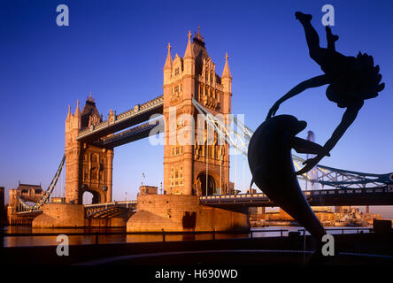Tower Bridge at dusk with Girl with a Dolphin statue, London - Stock Photo