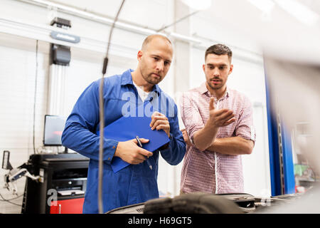auto mechanic with clipboard and man at car shop - Stock Photo