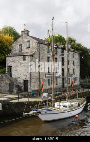 Adventure Activities Centre in old port warehouse beside Afon Teifi River with moored yacht on quay. Cardigan Wales - Stock Photo