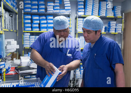 Two nurses in scrubs check medical equipment in the hospital storeroom including hip replacement sterile packs - Stock Photo