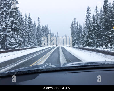 Driver's point of view viewpoint looking through car windshield of snowy road in winter driving - Stock Photo