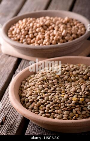 Vertical photo. Two clay plates. Two earthen bowls with legumes. Plates with lentils and chickpeas. Detail of legumes. - Stock Photo