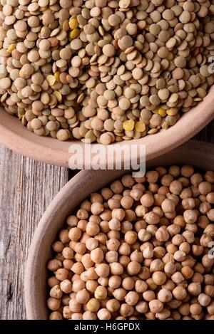 Vertical photo with top view. Two clay plates. Two earthen bowls with legumes. Plates with lentils and chickpeas. - Stock Photo