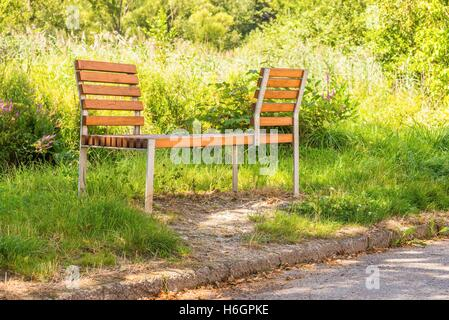 Horizontal photo of interesting bench from metal and wood which is placed on the lawn next to pavement (sidewalk). - Stock Photo