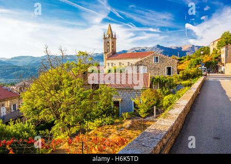 Church in Zonza village with typical stone houses during sunset, Corsica, France, Europe. - Stock Photo