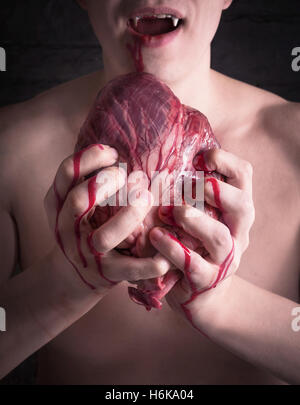 Vampire with blood on his face holding a heart in his hands and trying to bite it - Stock Photo