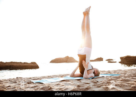Portrait of a young woman doing fitness exercises outdoors in the morning - Stock Photo