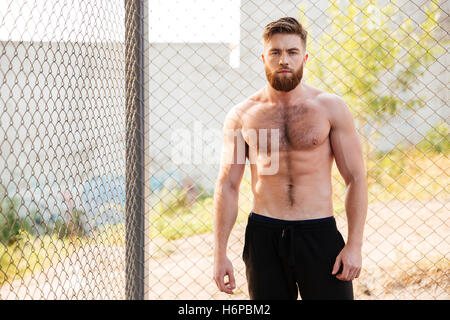 Handsome young shirtless fitness man during workout outdoors - Stock Photo