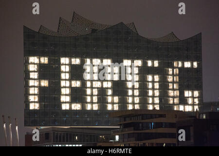 With several illuminated windows, the facade of the Elbphilharmonie spells out the word 'Fertig' (lit. 'Finished') - Stock Photo