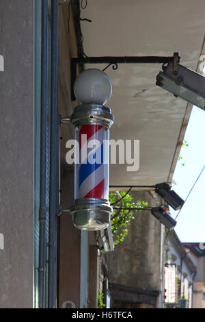 Traditional barber shop sign stripped hanging on wall outside hairdressers universal sign for male hair cutting - Stock Photo