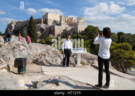 A tourist from China poses for a photograph on the Aeropagus with the Acropolis in the background - Stock Photo