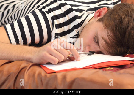 Tired student resting in his bedroom - Stock Photo