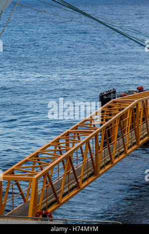 Yellow metal girder bridge across water at port - Stock Photo