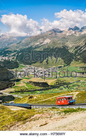 Cable car going up Muottas Muragl with the Upper Engadin Lakes in the background, Engadin, Switzerland - Stock Photo