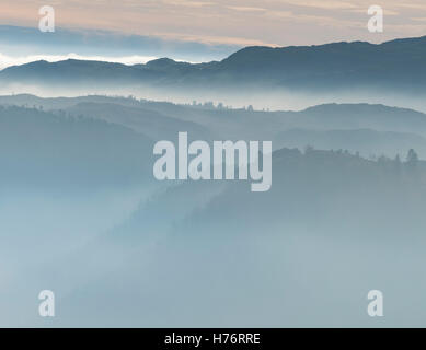 Hills and trees around Thirlmere above mist in the English Lake District, England, UK, view from Raven Crag - Stock Photo