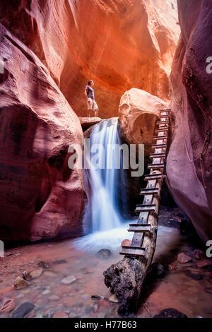 Woman standing above waterfall, red slot canyon, Utah, America, USA - Stock Photo
