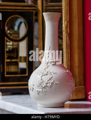 White oriental blossom vase on marble mantlepiece set against red wall in palladian 18th century Dumfries house, - Stock Photo