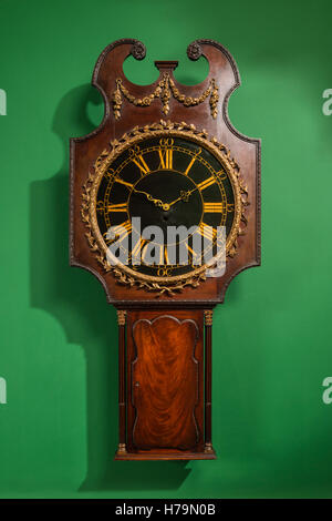 Antique wooden clock set on green wall in Dumfries house, Ayrshire, Scotland - Stock Photo